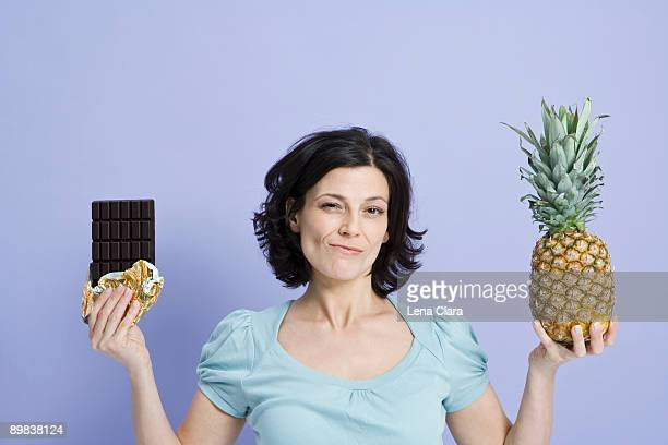 A woman deciding between a pineapple and a chocolate bar