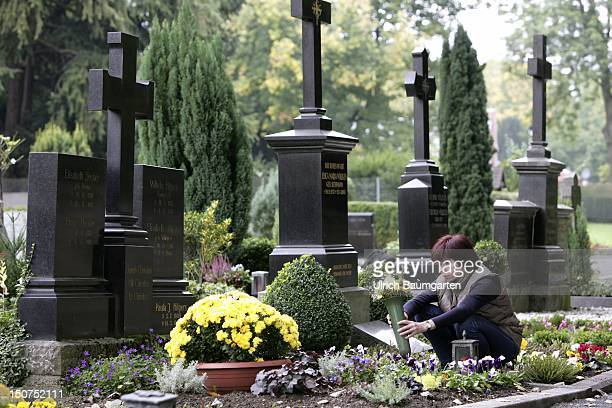 GERMANY BONN A woman decorates a grave with flowers on a cemetery