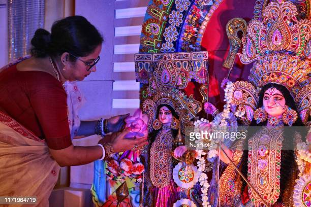 Woman decorates the idol the Goddess Durga with lotus flowers before prayers commence during the Durga Puja festival at a pandal in Mississauga...