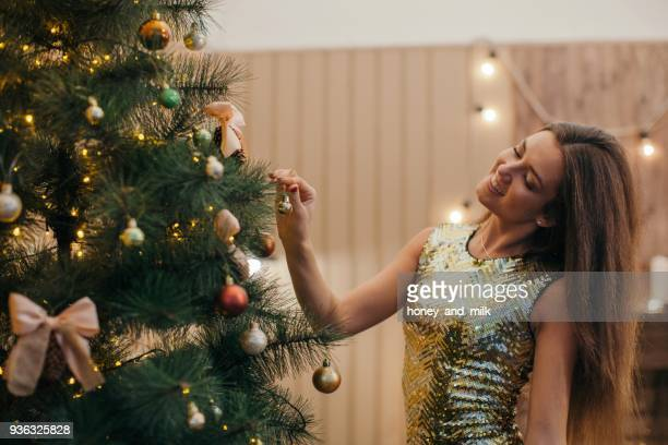 woman decorating a christmas tree - cocktail dress stock pictures, royalty-free photos & images