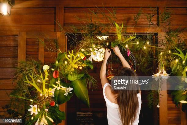 mujer decorando una guirnalda con hojas y flores para navidad - brazil nut fotografías e imágenes de stock