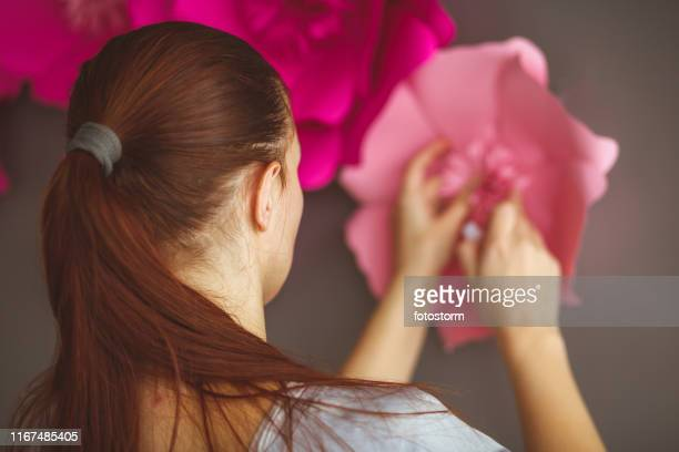 Woman decorating a wall with paper flowers