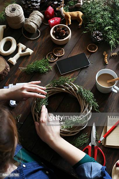 Woman decorating Advent wreath on work table, partial view