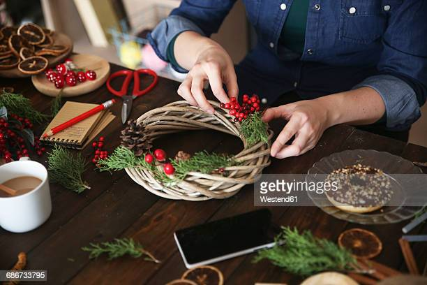 Woman decorating Advent wreath, partial view