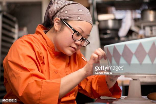 woman decorating cake at store - decorating a cake stock pictures, royalty-free photos & images