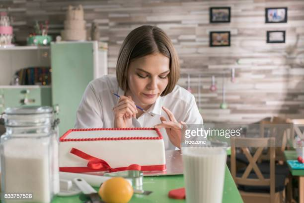 woman decorating cake - decorating a cake stock pictures, royalty-free photos & images
