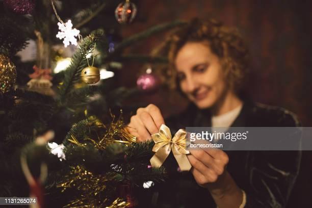 Woman Decorating Christmas Tree At Home
