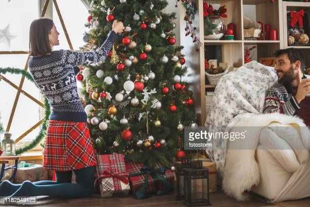woman decorating christmas tree, man sitting on sofa near her - silver skirt stock pictures, royalty-free photos & images
