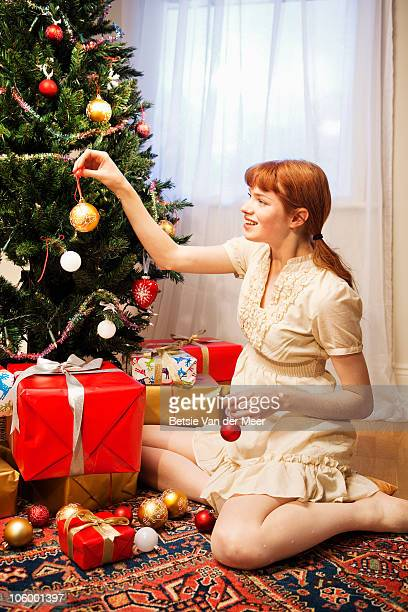 Woman decorating Christmas tree.