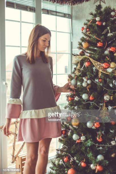vrouw versieren kerstboom - versierde jurk stockfoto's en -beelden