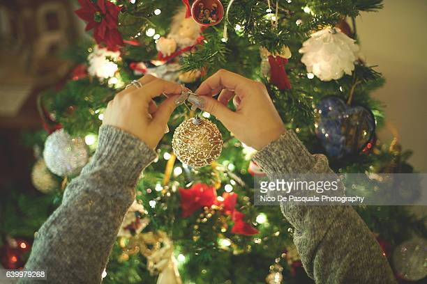 woman decorating christmas tree - decoration stock pictures, royalty-free photos & images