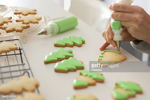 Woman decorating cookies with green colored icing