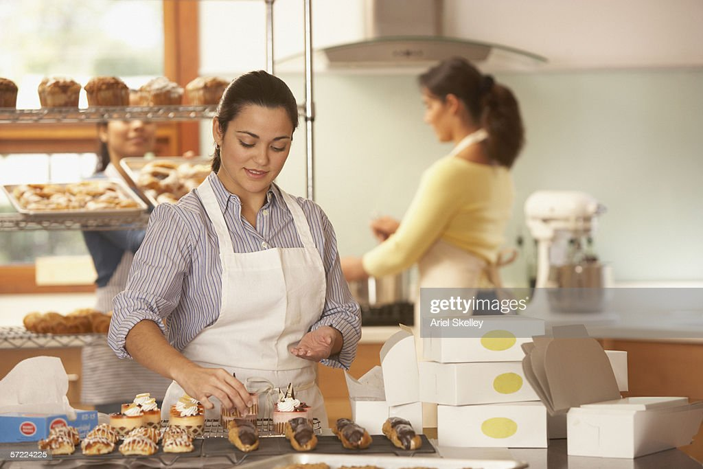 woman decorating cupcakes in bakery stock photo