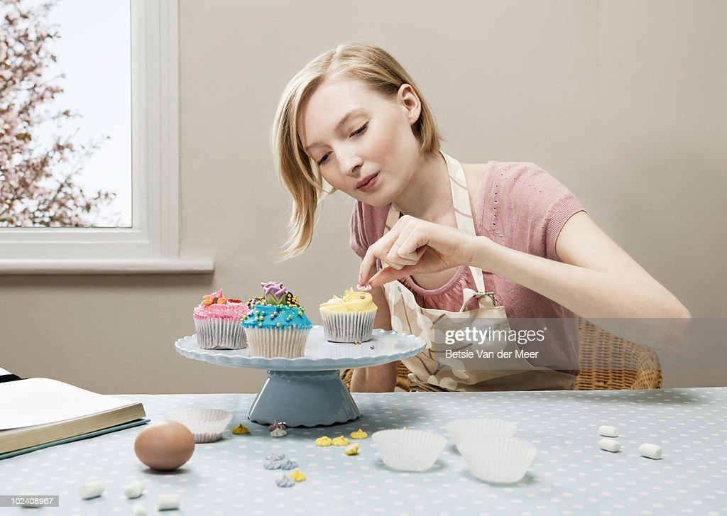 woman decorating cupcakes - Woman Decorating Cupcakes