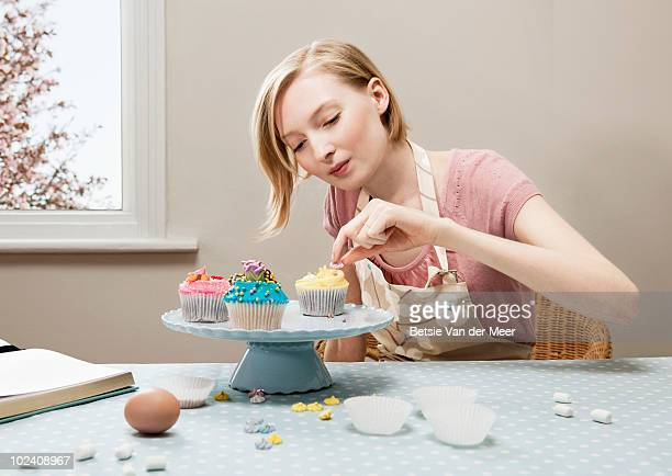 woman decorating cupcakes.