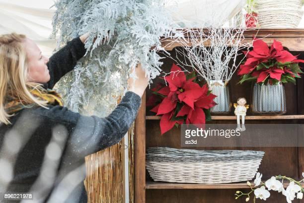 mujer decorar su tienda de flores - flor de pascua fotografías e imágenes de stock