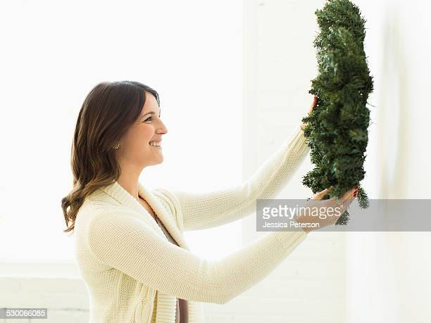 Woman decorating home with Christmas wreath
