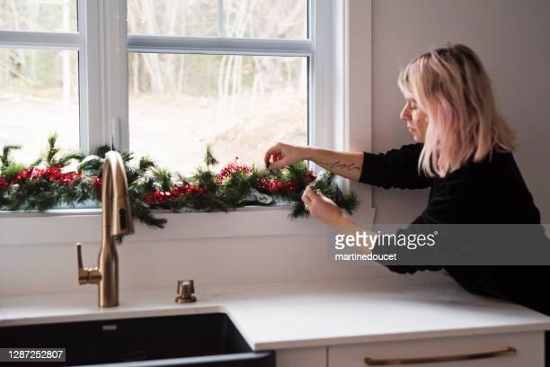"woman decorating kitchen window for christmas. - ""martine doucet"" or martinedoucet stock pictures, royalty-free photos & images"