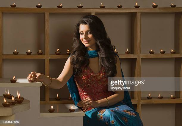 woman decorating oil lamps in diwali festival - diwali decoration stock pictures, royalty-free photos & images