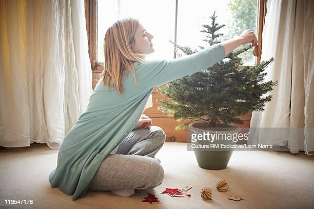 Woman decorating small Christmas tree