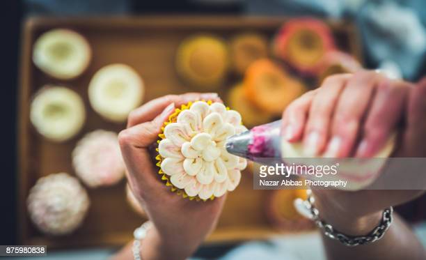 woman decoration cupcakes. - decorating a cake stock pictures, royalty-free photos & images