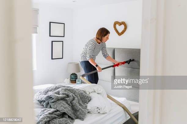 woman deep cleaning her bedroom - bed stock pictures, royalty-free photos & images