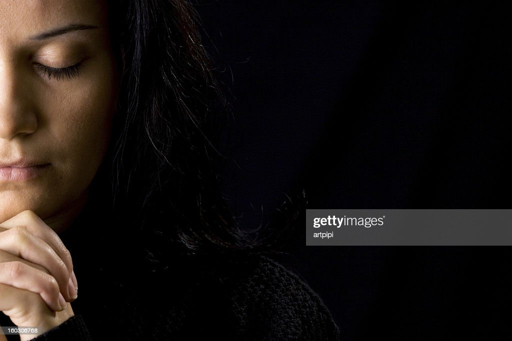 A woman deep in prayer and a black background : Stock Photo