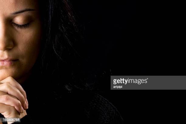 a woman deep in prayer and a black background - praying stock pictures, royalty-free photos & images