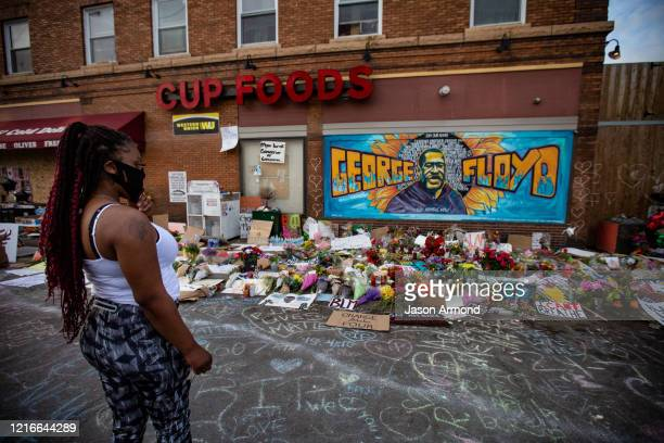 A woman defies curfew to pay her respects at the makeshift memorial and mural outside Cup Foods where George Floyd was murdered by a Minneapolis...