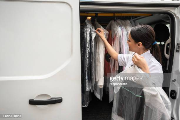woman delivering dry cleaned clothes - dry cleaned stock pictures, royalty-free photos & images