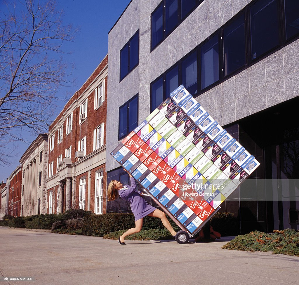 Woman delivering heavy boxes, side view : Foto stock
