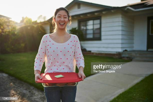 woman delivering homemade cookies to neighbor - neighbour stock pictures, royalty-free photos & images
