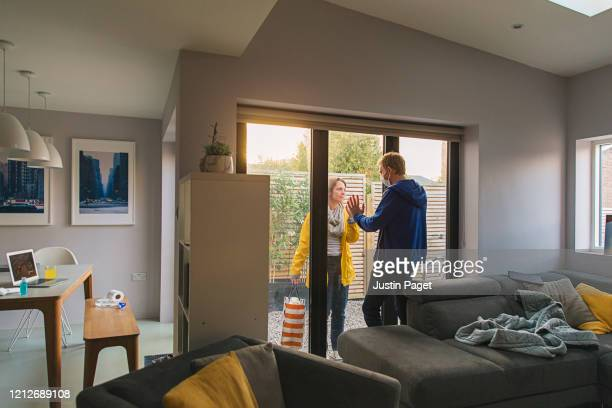 woman delivering items to her husband who is in self isolation at home - pandemic illness stock pictures, royalty-free photos & images