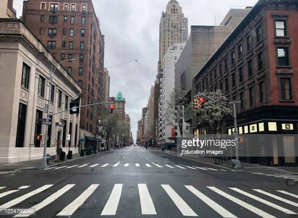 Woman delivering mail during the Coronavirus lockdown period, walking along Broadway wearing a mask and gloves for protection, Manhattan, New York,...