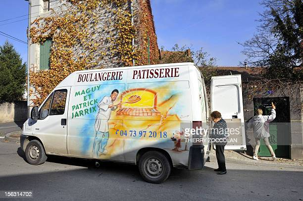A woman delivers bread next to a truck used as a mobile bakery on November 13 2012 in La Moutade central France AFP PHOTO THIERRY ZOCCOLAN
