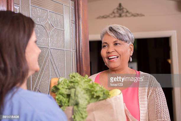 woman delivers groceries to senior adult woman at home. - meals on wheels stock pictures, royalty-free photos & images