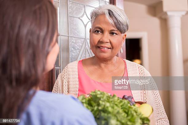 Woman delivers groceries to senior adult woman at home.
