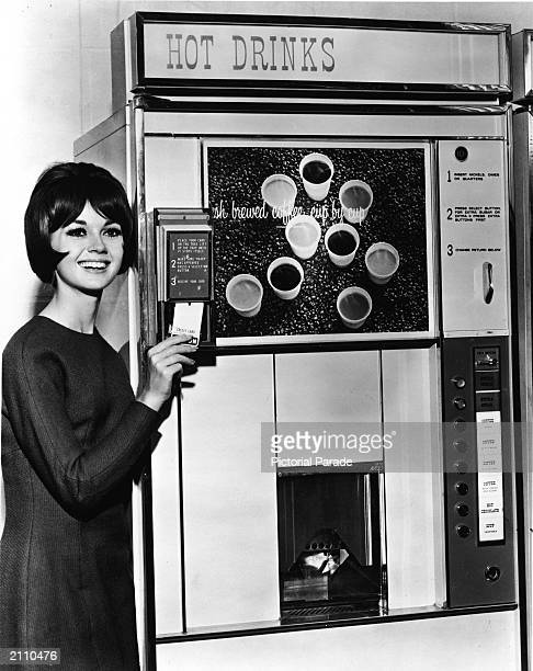A woman demonstrates a cardoperated coffee and hot drink vending machine circa 1960