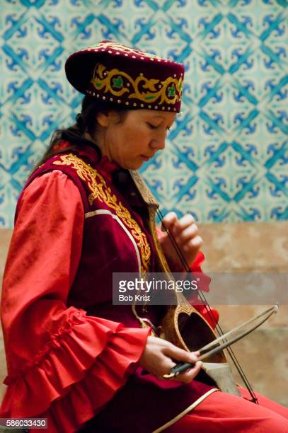 A woman demonstrates a traditional instrument at Ykhlas Republican Museum of Folk Musical Instruments, Almaty, Kazakhstan