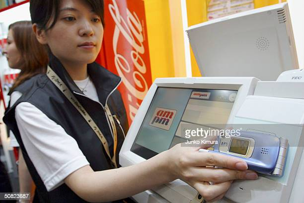 A woman demonstrates how to buy products at a convenience store paying with your phone rather than a ticket during a business show on May 11 2004 in...