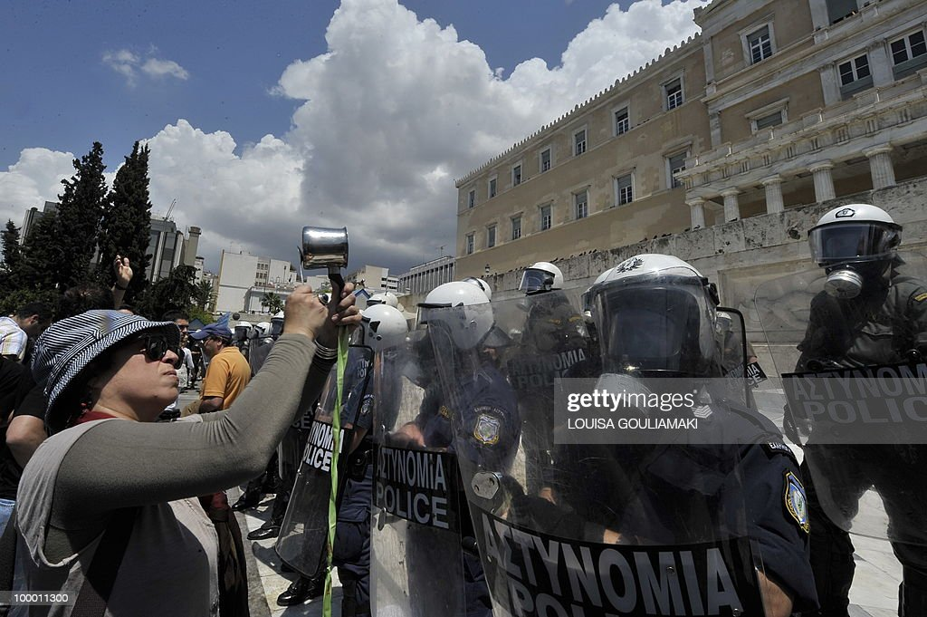 A woman demonstrates in front of riot police deployed at the Greek Parliament in Athens during the 24-hour general strike against the austerity measures on May 20, 2010. Thousands of protesters took to the streets of Athens and second city Thessaloniki on Thursday in a new general strike against the government's debt-dictated austerity spending cuts and pension reform. AFP PHOTO / Louisa Gouliamaki