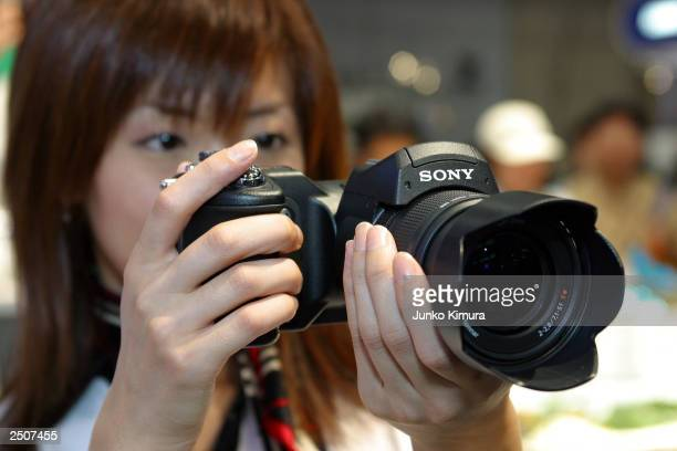 Woman demonstrates Sony's newly introduced eight million-pixel digital camera the Cyber-Shot digital camera DSC-F828 during Asia's biggest digital...