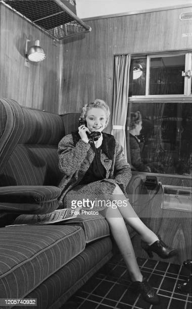 A woman demonstrates using a phone aboard the new Coronation Scot train on view at Euston Station London UK 9th January 1939