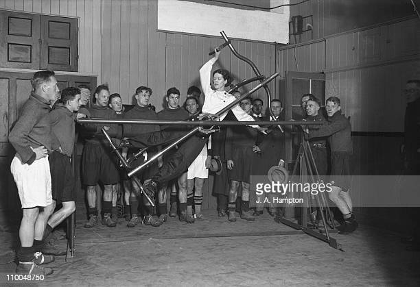 Woman demonstrating an excercise machine, known as the Gymo Frame, to members of the Arsenal football team at their gym at Highbury football ground,...