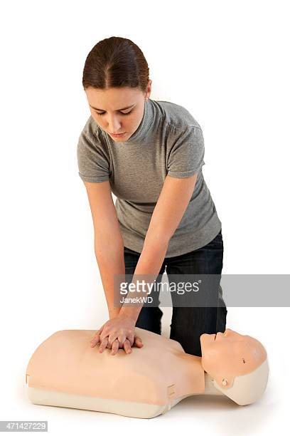 Woman demonstrating how to do chest compressions on a dummy