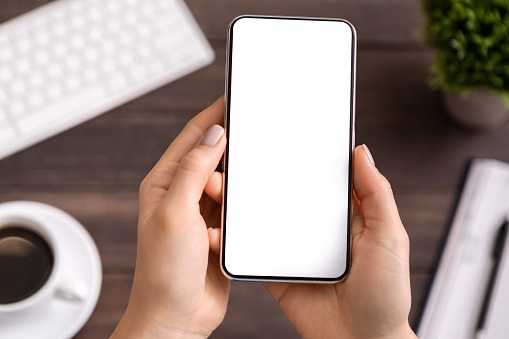 Woman demonstrating modern smartphone with blank white screen 1174433187