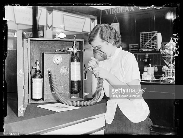 Woman demonstrating portable pain relief apparatus 1937 A photograph of a woman demonstrating portable apparatus for pain relief taken by Barnet...
