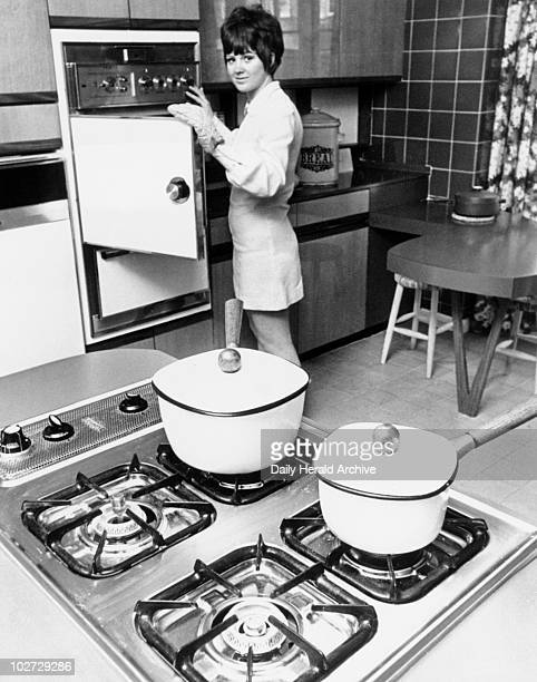 Woman demonstrating the latest cooker techn Woman demonstrating the latest cooker technology 8 June 1969 'Modern kitchen with electric oven and grill...
