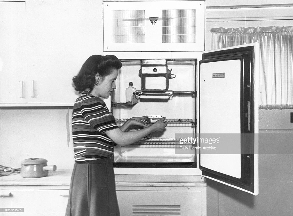 Woman demonstrating the latest refrigerator, 1946. : News Photo