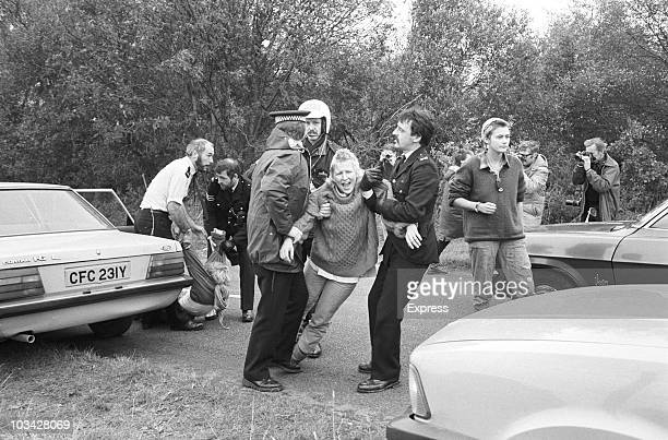 A woman demonstrator is arrested during protests by antinuclear campaigners opposed to the deployment of the nuclear missiles at Greenham Common air...